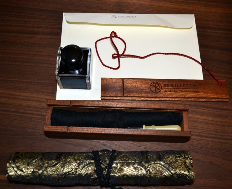 A beautiful wood box containing the pen, eye dropper and instructions, as well as a bottle of ink (which leaked a bit), and a nice pen wrap.